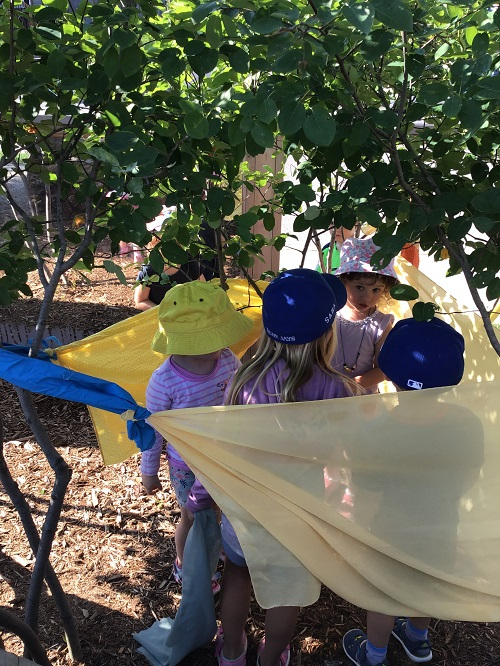 Children making a fort out of scarves